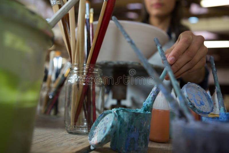 Kvinnlig keramiker som målar en bunke fotografering för bildbyråer