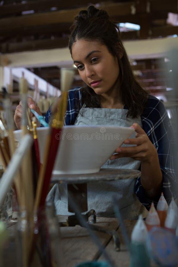 Kvinnlig keramiker som målar en bunke arkivbilder