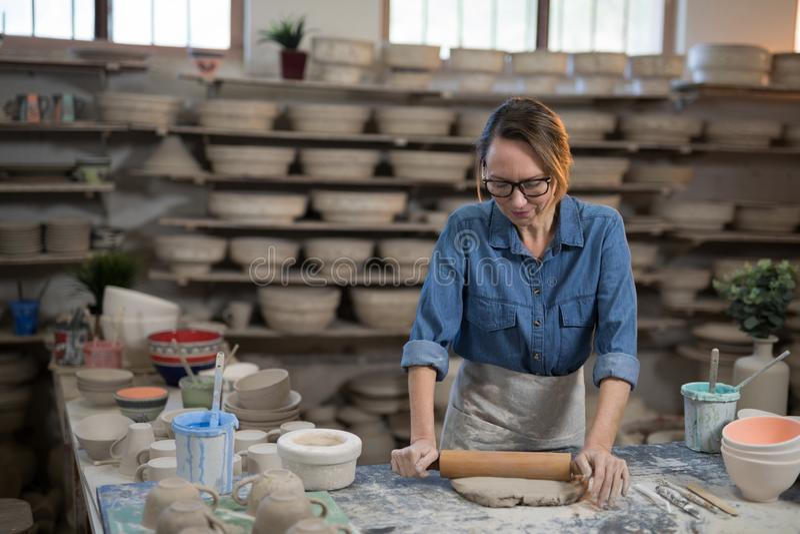 Kvinnlig keramiker som slätar leran med kavlen ut arkivfoton