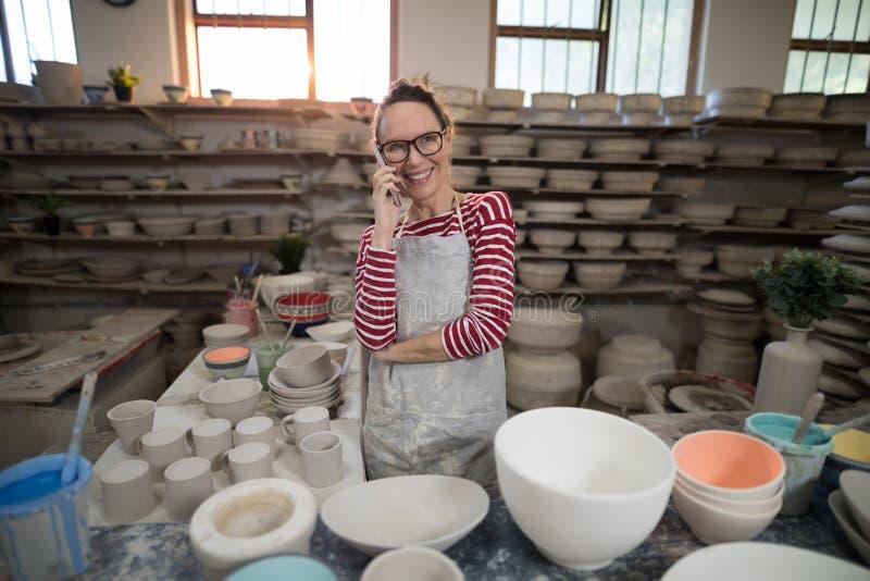 Kvinnlig keramiker som talar på mobiltelefonen fotografering för bildbyråer