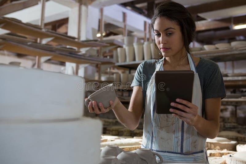 Kvinnlig keramikerinnehavkopp, medan genom att använda den digitala minnestavlan fotografering för bildbyråer