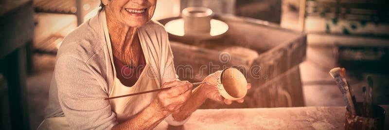 Kvinnlig keramikermålning på bunken royaltyfri fotografi
