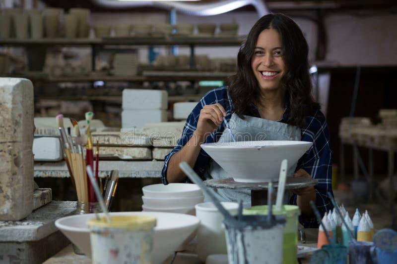 Kvinnlig keramikermålningbunke med målarfärgborsten royaltyfria bilder