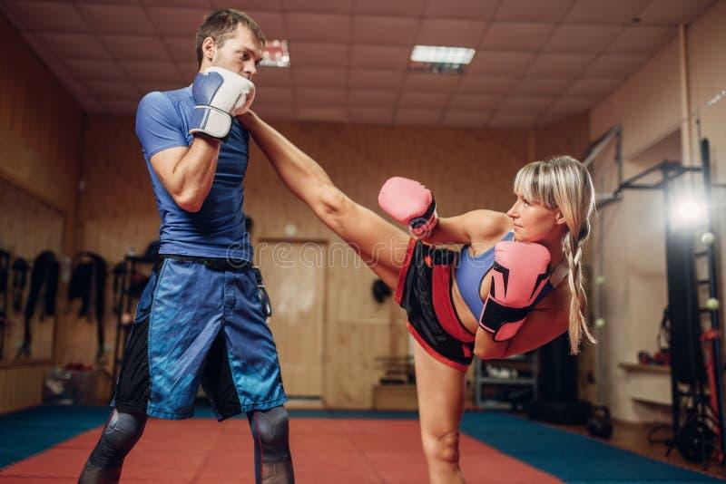 Kvinnlig kickboxer med den manliga personliga instruktören arkivbild