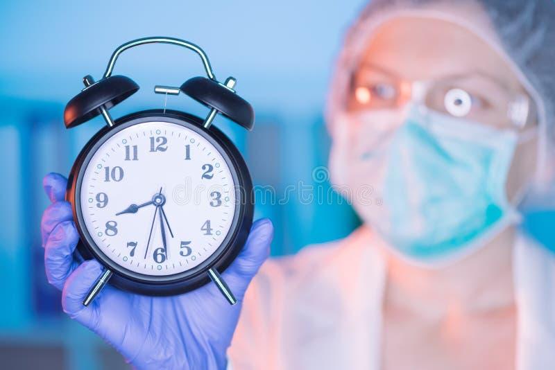 Kvinnlig kirurg med klockan arkivfoto