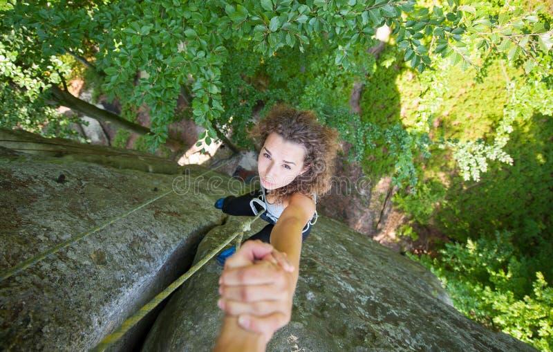 Kvinnlig klättrare för klättrareportion som når ett maximum av berget arkivbild