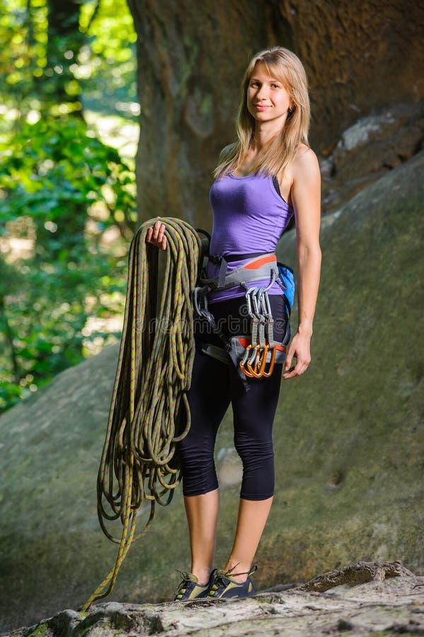 Kvinnlig klättrare som rymmer repet nära den stora stenblocket arkivbild