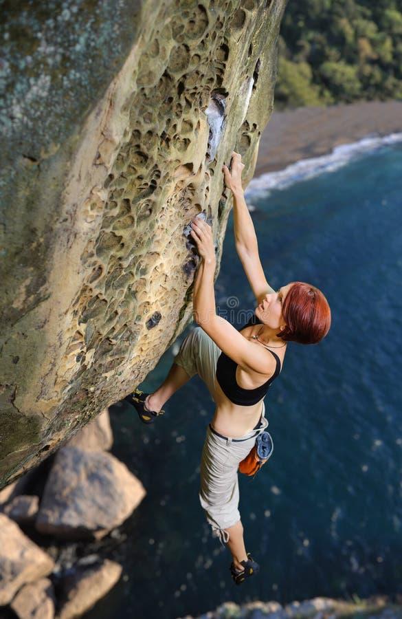 Kvinnlig klättrareklättring utan rep på en stenig vägg royaltyfri fotografi