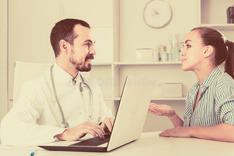 Kvinnlig klient som besöker konsultation med mandoktorn arkivfoto