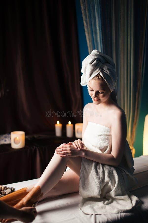 Kvinnlig klient som har chokladvikten på fötter under massage i brunnsortsalong royaltyfria foton