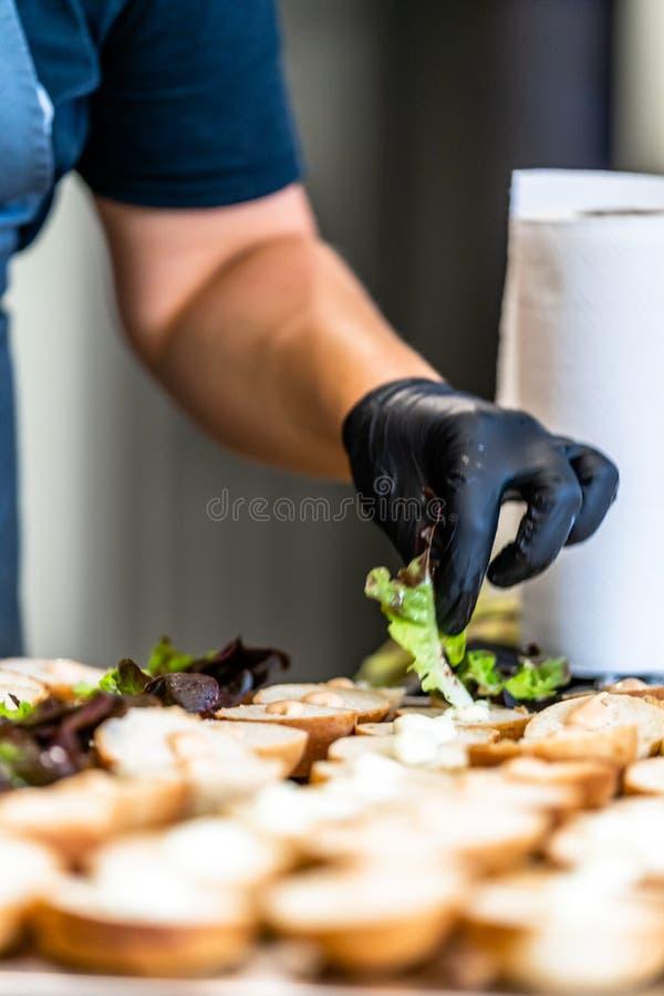 Kvinnlig kock Putting Ingredients av hamburgare på en skivad brödspridning på en tabell i svarta handskar - begrepp av det hårda  royaltyfria bilder