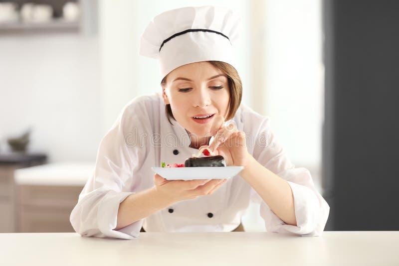Kvinnlig kock som dekorerar den smakliga efterrätten arkivbilder