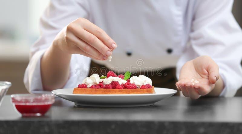 Kvinnlig kock som dekorerar den smakliga efterrätten i kök arkivfoton