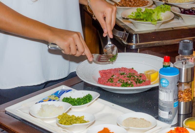 Kvinnlig kock som förbereder bifftandsten i kök med en special sås arkivfoton