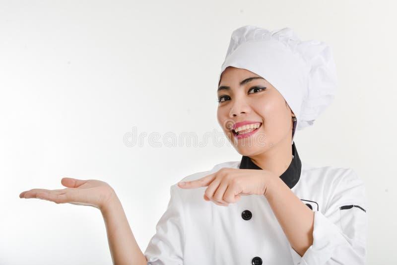 Kvinnlig kock som framlägger menyn Den gulliga flickakocken i huven visar ett H arkivfoto