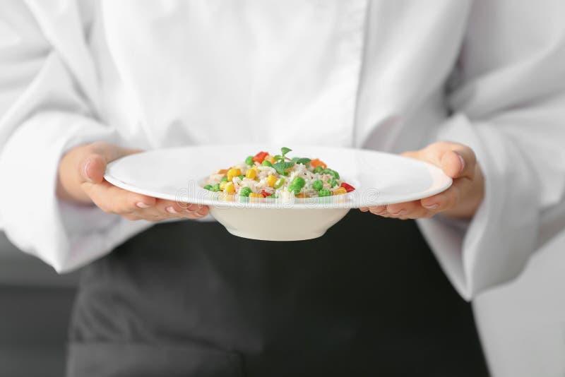 Kvinnlig kock som rymmer den förberedda maträtten arkivbilder