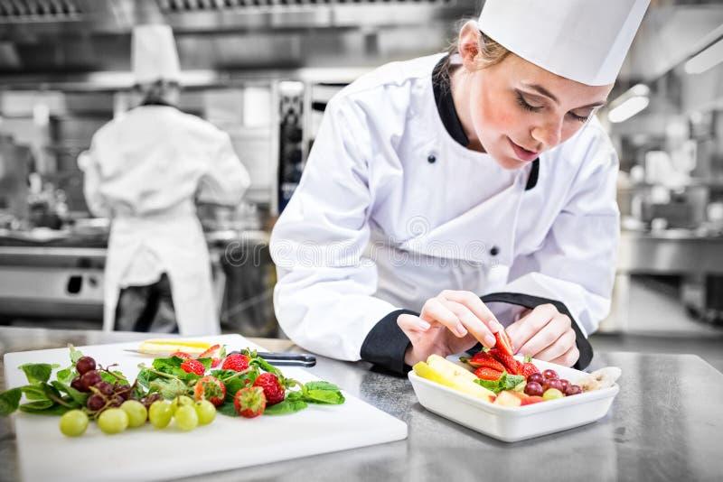 Kvinnlig kock som sätter en jordgubbe i fruktsalladen royaltyfri fotografi