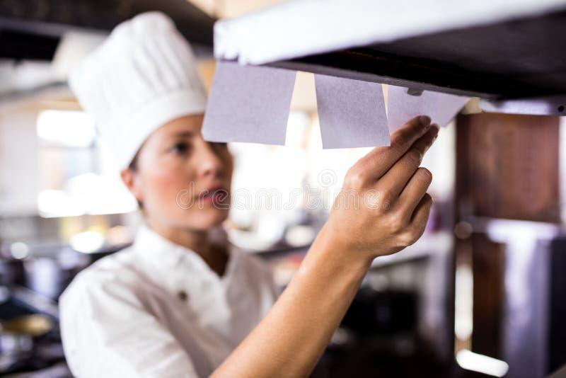 Kvinnlig kock som ser beställningslistan i kök royaltyfri bild