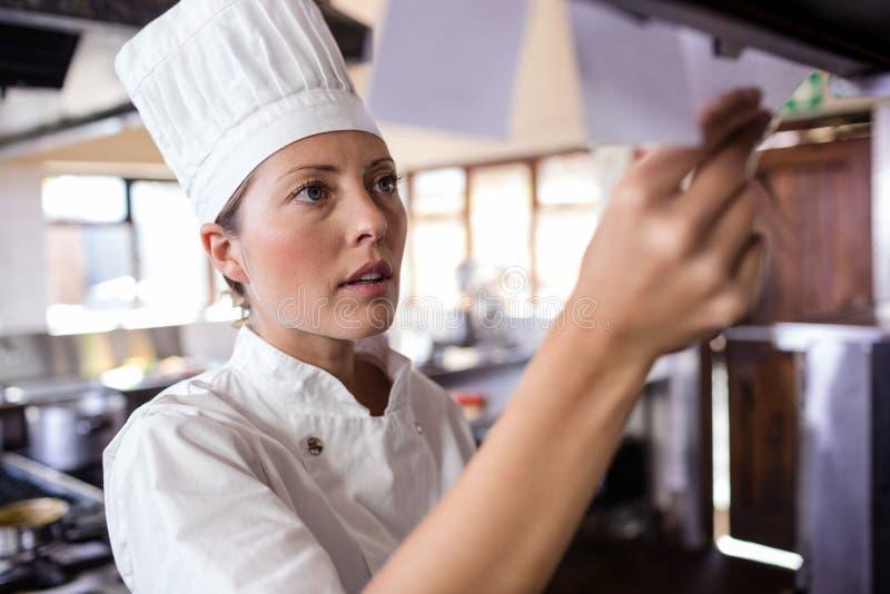 Kvinnlig kock som ser beställningslistan i kök fotografering för bildbyråer
