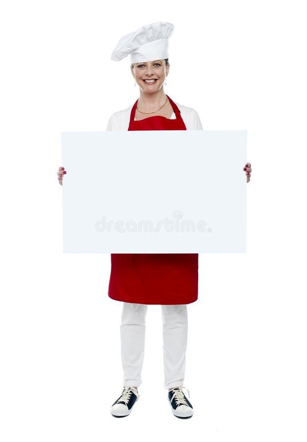 Kvinnlig kock som visar det tomma vita annonsbrädet royaltyfria bilder