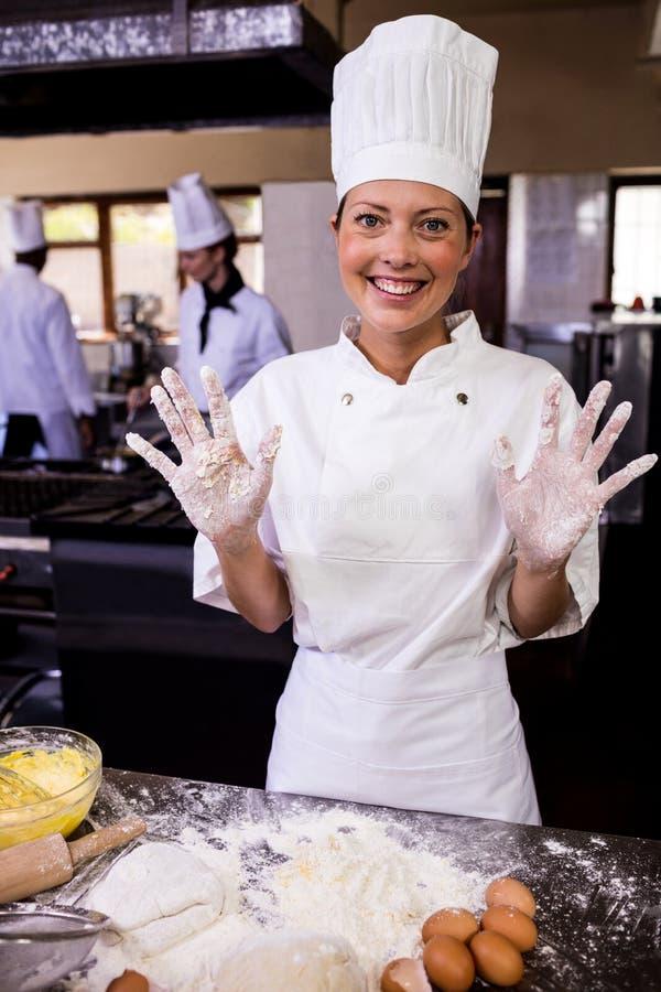 Kvinnlig kock som visar hennes smutsiga händer i kök royaltyfri fotografi