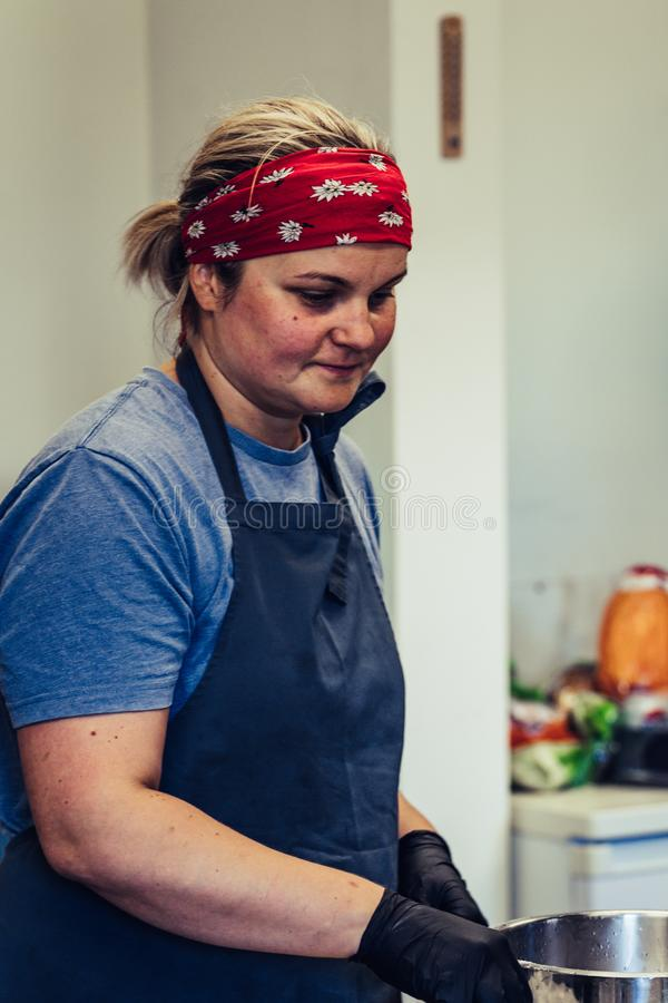 Kvinnlig kock Taking ett avbrott från den frustrerade målförberedelsen -, bekymrat, begrepp av en hård funktionsduglig person royaltyfria bilder