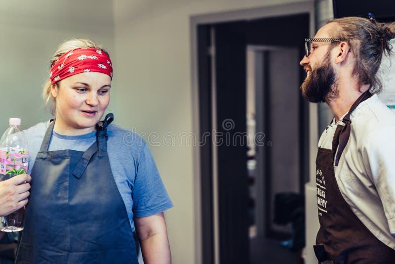 Kvinnlig kock Taking ett avbrott från målförberedelsen, Odziena/Lettland - Augusti 24th, 2018: Diskutera process med den lyckliga arkivfoto