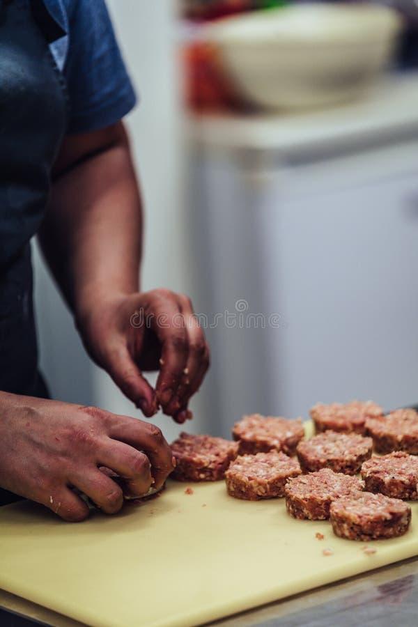 Kvinnlig kockMaking Round Pork kotlett för några hamburgare för att gifta sig mål royaltyfria foton