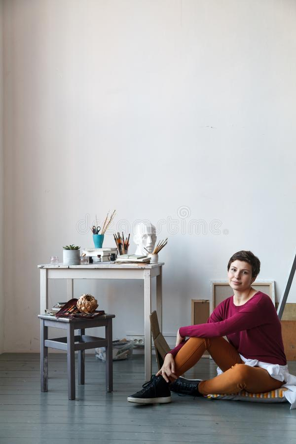 Kvinnlig konstnär i hennes rymliga vita studio som arbetar med vattenfärgmålning arkivbilder