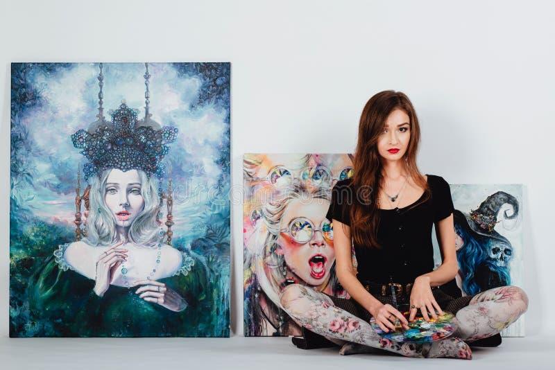 Kvinnlig konstnär på bildkanfas på vit bakgrund Flickamålare med borstar och paletten Konstskapelsebegrepp royaltyfri foto