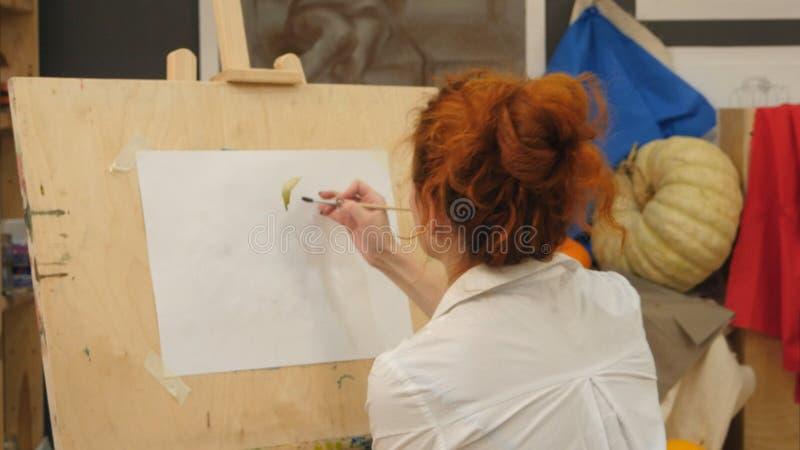 Kvinnlig konstnär som arbetar på vattenfärgmålning i studio arkivfoto