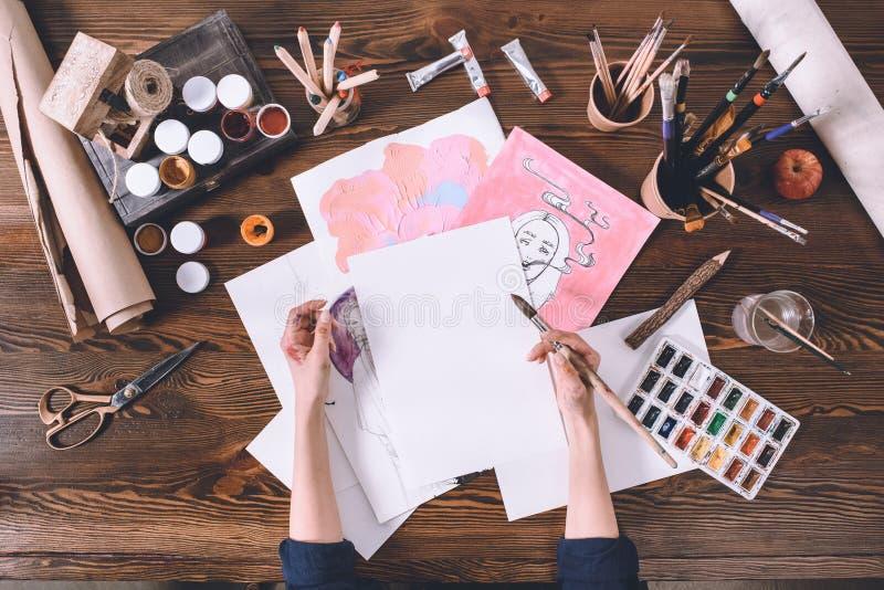 Kvinnlig konstnärmålning skissar på arbetsplatsen med målarfärger och borstar arkivfoton