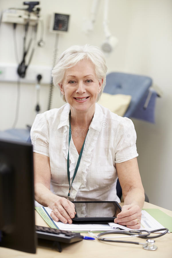 Kvinnlig konsulent Working At Desk som använder den Digital minnestavlan arkivfoto