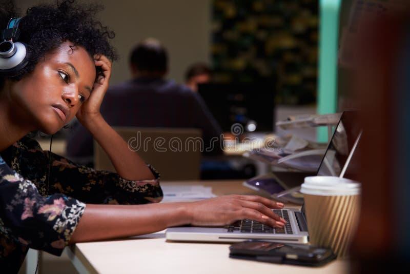 Kvinnlig kontorsarbetare med kaffe på skrivbordet som sent arbetar royaltyfria foton