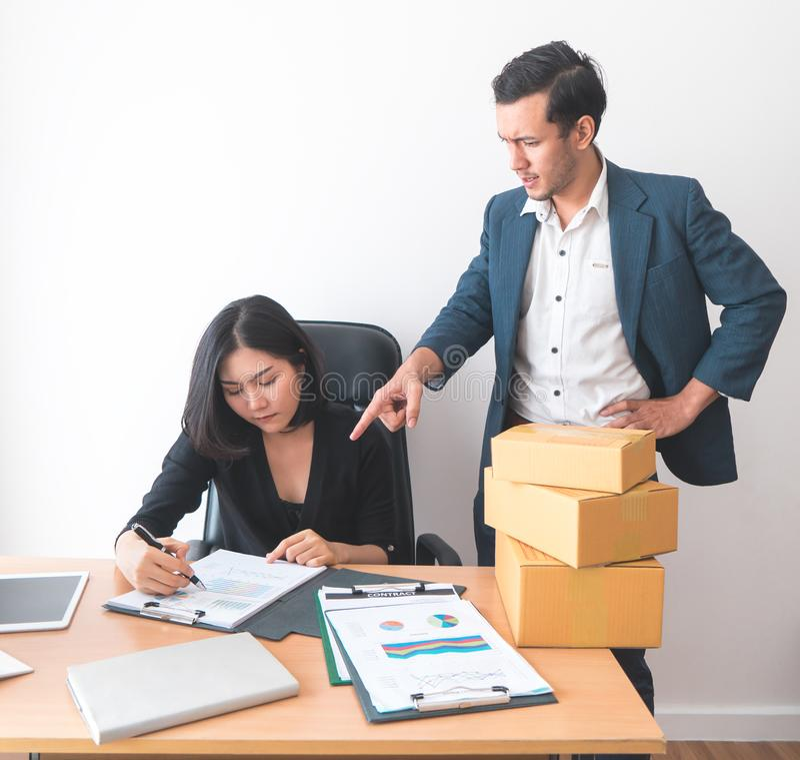 Kvinnlig kontorsarbetare som arbetar under tryck från arbetsledare arkivfoton