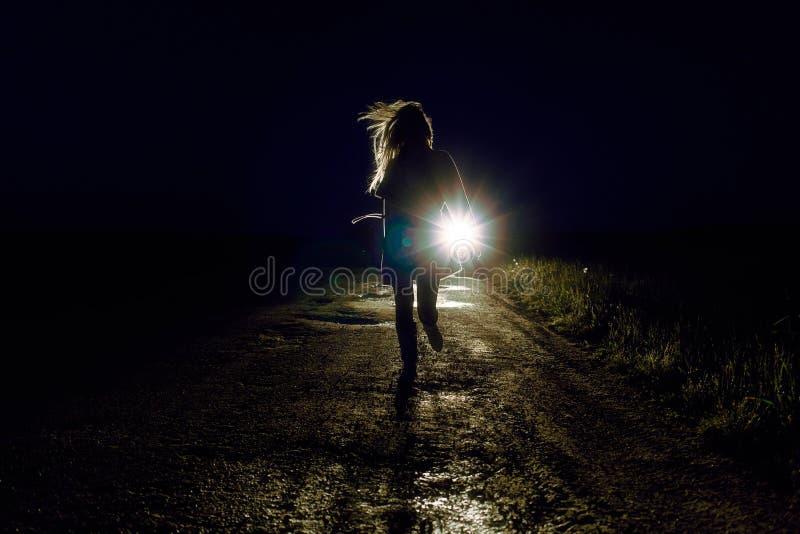 kvinnlig kontur på en spring för nattlandsväg i väg från förföljare med bilen i ljuset av billyktor royaltyfri fotografi