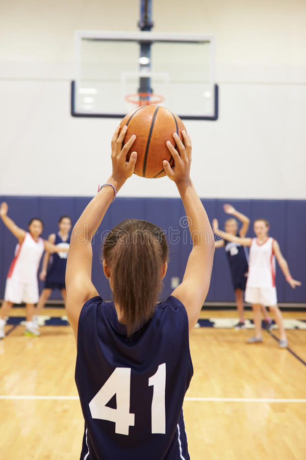 Kvinnlig korg för skytte för högstadiumbasketspelare royaltyfria foton