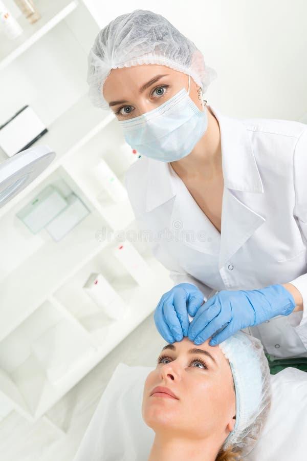 Kvinnlig kosmetologdoktor med patienten i wellnessmitt E royaltyfri foto
