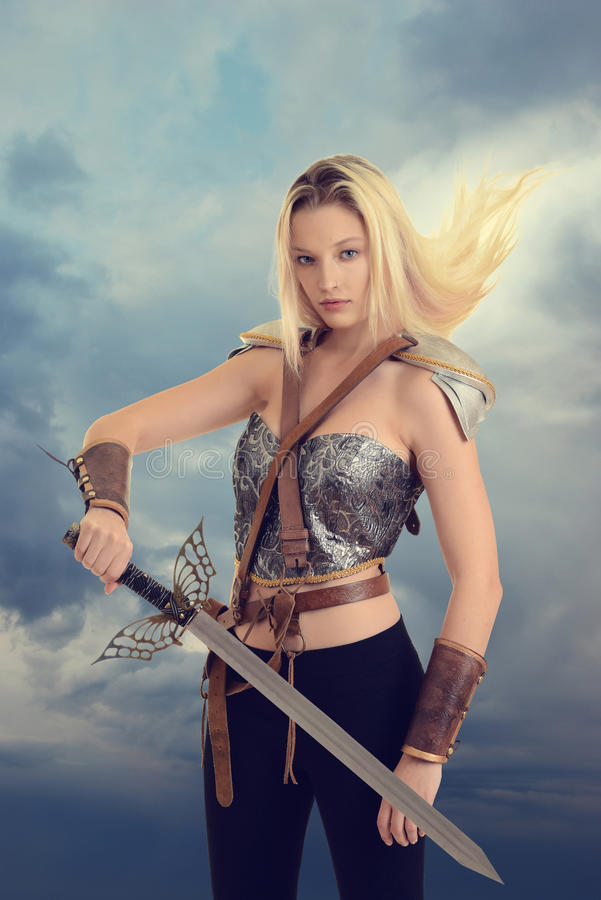Kvinnlig krigare med svärdet och hår som blåser i vind royaltyfria bilder