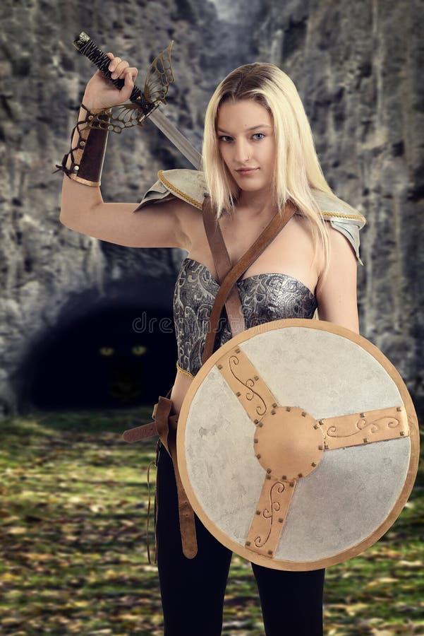 Kvinnlig krigare som får klar att slåss en drake royaltyfria bilder