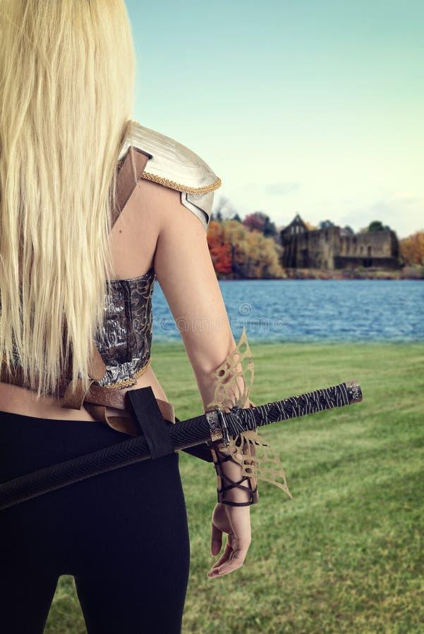 Kvinnlig krigare som ser över en sjö på slotten royaltyfri bild