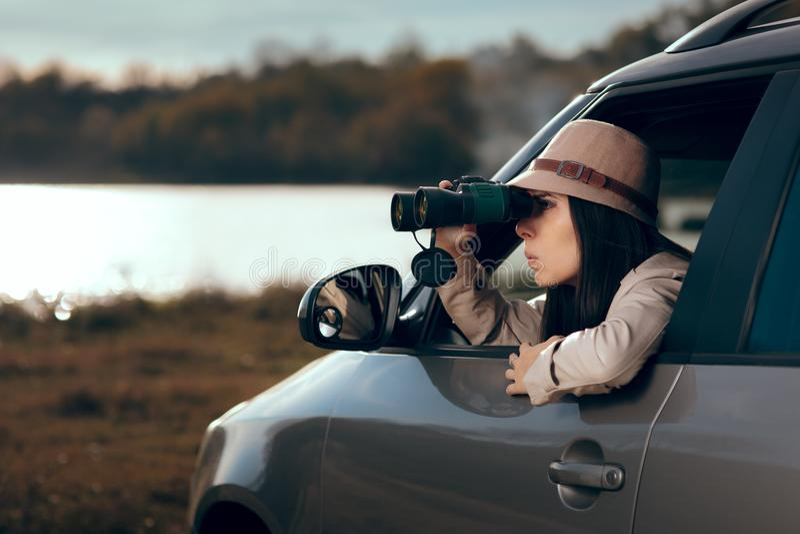 Kvinnlig kriminalare Spying med binokulärt från en bil royaltyfria foton
