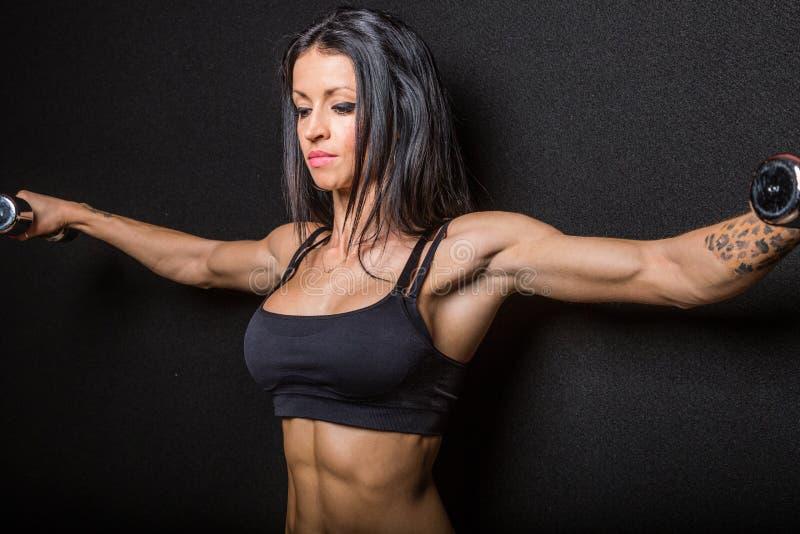 Kvinnlig kroppsbyggare som böjer muskler med vikter arkivbild