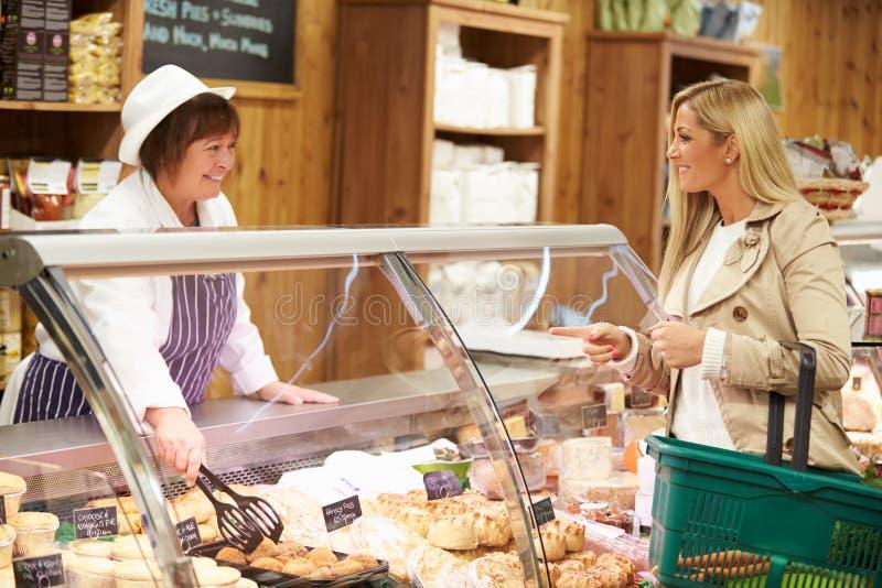 Kvinnlig kund för försäljningsassistentportion i matvaruaffär royaltyfri bild