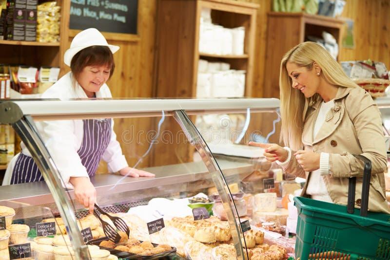 Kvinnlig kund för försäljningsassistentportion i matvaruaffär royaltyfri foto