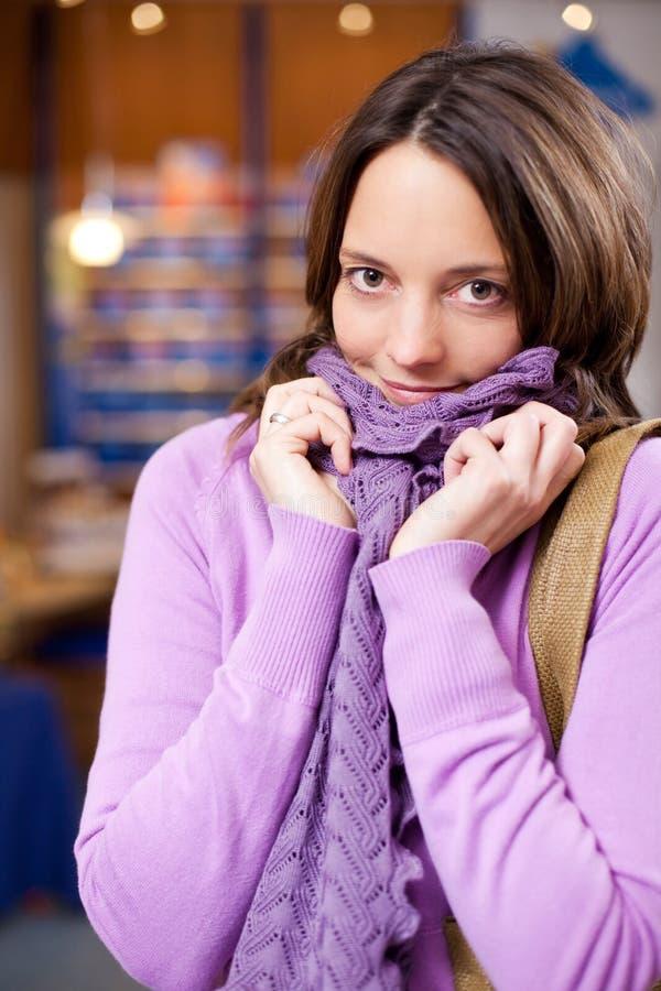 Kvinnlig kund i tröja- och halsdukfrossa på apotek royaltyfria bilder
