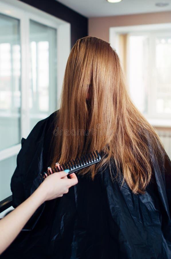 Kvinnlig kund med långt rakt ganska hår som skrattar, medan en frisör som ut kammar, strandar framme av hennes framsida royaltyfria bilder