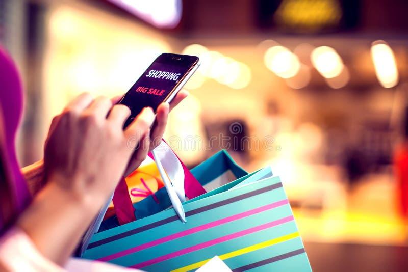 Kvinnlig kund med mobiltelefon- och shoppingpåsar i malen royaltyfri bild