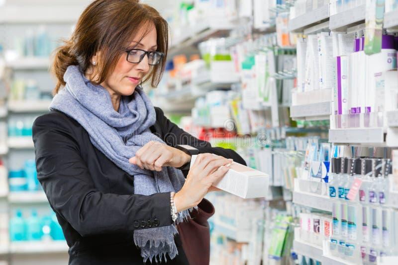 Kvinnlig kundscanningprodukt till och med smartwatch i apotek arkivfoto