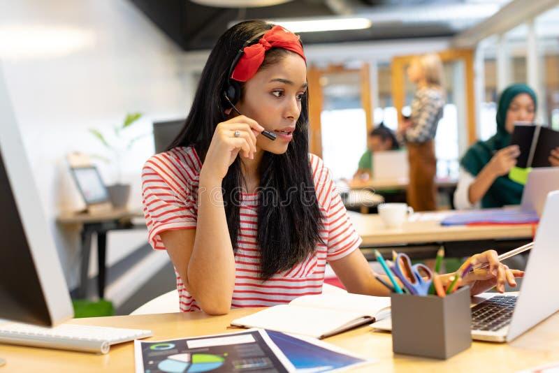 Kvinnlig kundtjänstledare som talar på hörlurar med mikrofon och arbetar på bärbara datorn i ett modernt kontor arkivbild